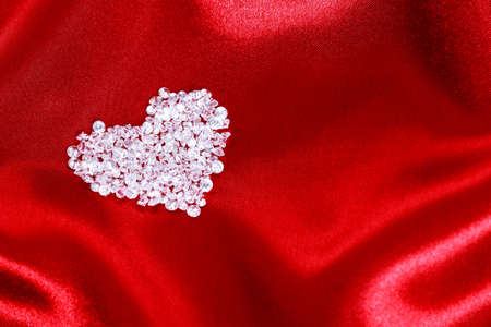 Heart shape made from CZ diamonds on a red satin background. Stock Photo - 17372626