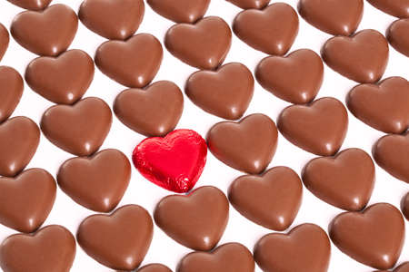 Rows of chocolate hearts with one odd one still in it's red foil wrapper, white background. Stock Photo - 17372594
