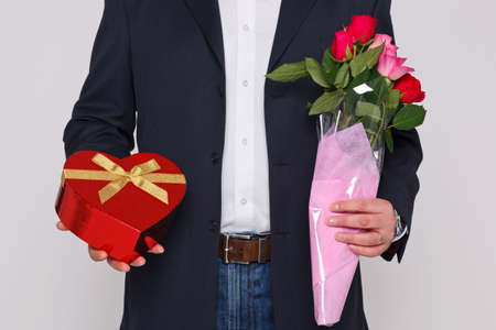 Man holding a bunch of flowers and a heart shaped box of chocolates. Stock Photo - 17362506