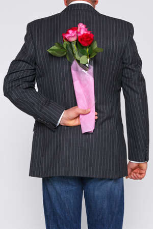 gift behind back: A man with a bunch of roses behind his back, the flowers are a surprise for someone.