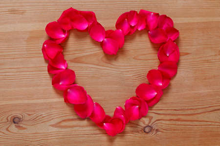 Heart shape made from red rose petals placed upon on a rustic wooden background.