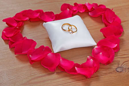 rose ring: Gold wedding and engagement ring on a small white cushion surrounded by a rose petal heart on a wooden background.