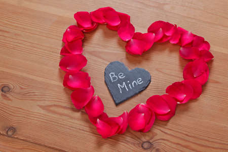 Red rose petals and slate in a heart shape with a romantic love message 'Be Mine'  Stock Photo - 17372604