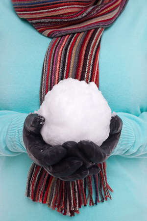 Woman wearing a knitted scarf and gloves holding a snowball. Stock Photo - 17567387
