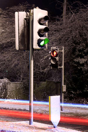 Traffic lights covered in snow on a UK road at night with light trails from passing cars. Stock Photo - 17681955