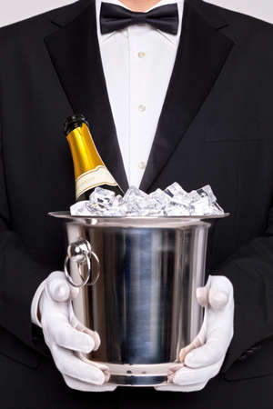 Waiter holding a wine cooler with a bottle of Champagne on ice photo