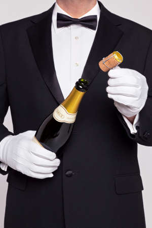 Waiter opening a bottle of champagne holding the cork in his other hand. photo