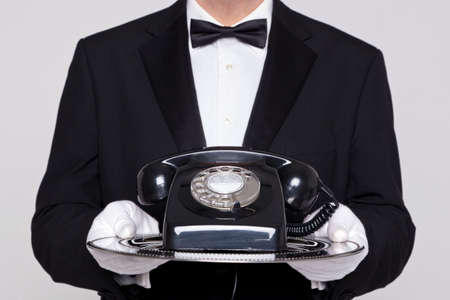 phonecall: Butler holding a silver tray with an old retro black telephone on it.