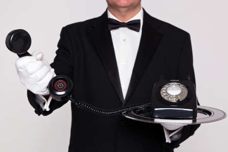 landline phone: Butler handing you the receiver from a retro telephone upon a silver serving tray.