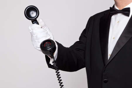 Butler holding the handset from a telephone Stock Photo - 17727198