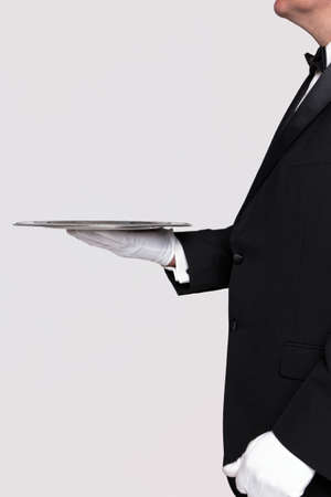 Side view of a butler holding a silver serving tray, blank background to add your own product.