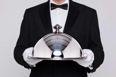 trays: Ober serveren van een maaltijd onder een zilveren cloche of koepel