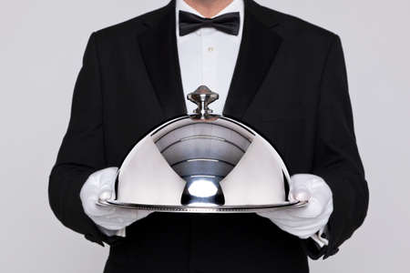 cloche: Waiter serving a meal under a silver cloche or dome