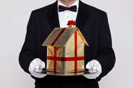 Butler holding a gift wrapped model building on a silver tray, good concept image for Moving, New Home, Relocation or House buying themes.