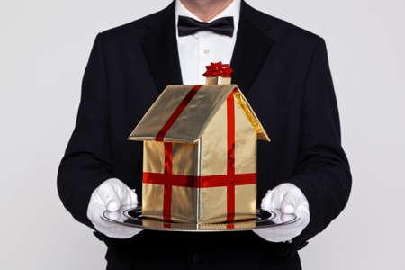sirvientes: Mayordomo que sostiene un regalo envuelto construcción de modelos en una bandeja de plata de la imagen, buen concepto de movimiento, casas nuevas Reubicación, o Casa de comprar temas.