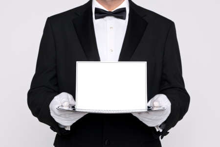 Butler holding a blank card upon a silver service tray, add your own message. photo