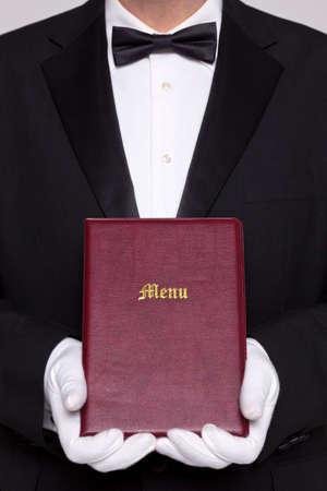 tie tuxedo: Waiter holding a Menu folder in a restaurant. Stock Photo