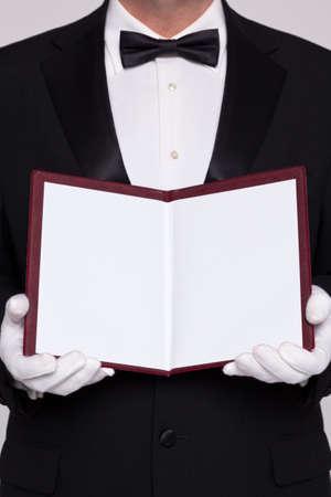 Cameriere che tiene aperto un menu in bianco per voi di aggiungere voi proprio testo per il cibo o una lista di vini.