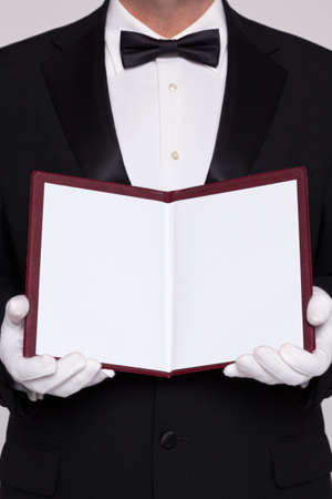 Waiter holding open a blank menu for you to add you own text for food or a wine list. photo