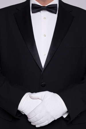 bow tie: Torso de un hombre que llevaba un esmoquin con pajarita y guantes blancos.