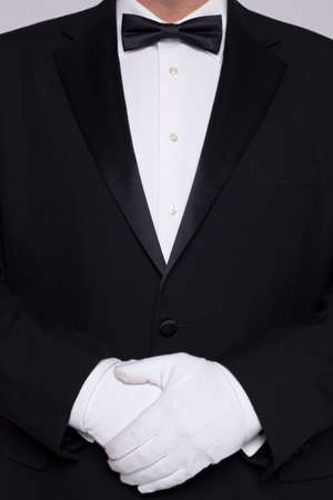 Torso of a man wearing a tuxedo with bow tie and white gloves. photo