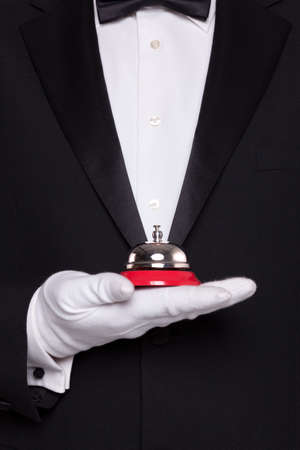 Waiter in black tie and white gloves holding a service bell. Stock Photo