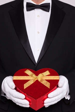 Man wearing black tie and white gloves holding a red heart shaped box of chocolates. photo