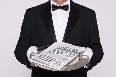 Butler delivering your Daily Newspaper. The paper is a mock up and all the names, titles, news headlines and articles are ficticious. Stock Photo - 17833917