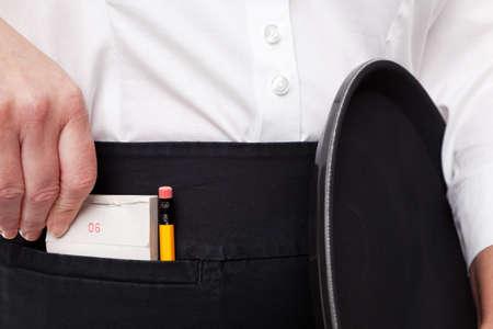 delantal: Primer plano de una camarera toma su cuaderno de orden en el bolsillo de su delantal mientras sostiene una bandeja en la otra mano. Foto de archivo