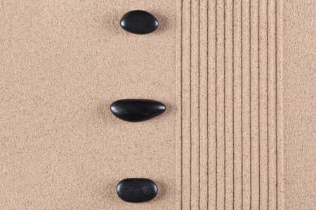 Three black pebbles on a raked sand zen garden. Stock Photo - 17833934