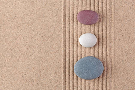 Three coloured pebbles on a raked sand zen garden. photo