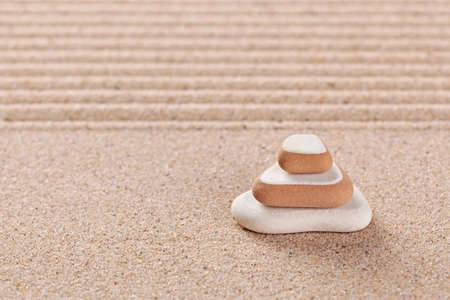 Three pebbles stacked on a raked sand zen garden. photo