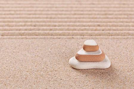 Three pebbles stacked on a raked sand zen garden. Stock Photo - 17833922
