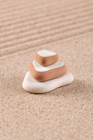 Three stones stacked on a raked sand zen garden. photo