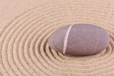 A single pebble in a raked sand circle zen garden. Stock Photo - 17833930
