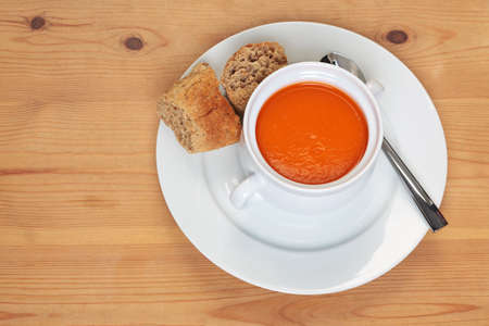 Bowl of hot tomatoe soup with fresh brown granary bread on a wooden table. Stock Photo - 18240313