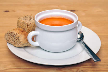 Bowl of hot tomatoe soup with fresh brown granary bread on a wooden table. Stock Photo - 18240312