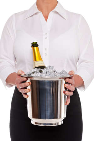 Waitress holding an ice bucket with a bottle of Champagne in it, isolated on a white background. photo