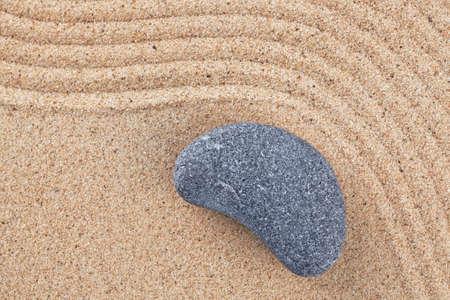 A curved pebble on a raked sand zen garden Stock Photo - 18367365