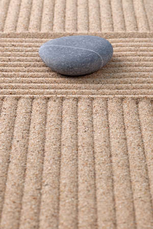 A pebble on a raked sand zen garden looking along the furrows. Stock Photo - 18367373