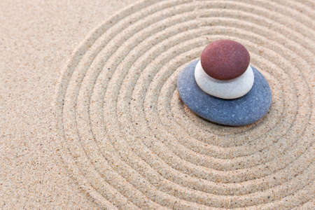 Three pebbles stacked on a circular raked zen garden photo