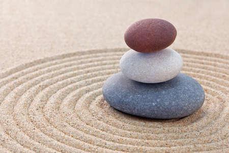 Three pebbles stacked on a circular raked zen garden Standard-Bild