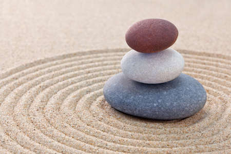 Three pebbles stacked on a circular raked zen garden Stock Photo - 18367369