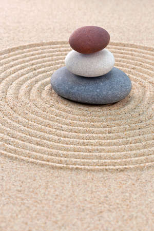 zen garden: Three pebbles stacked on a circular raked zen garden Stock Photo