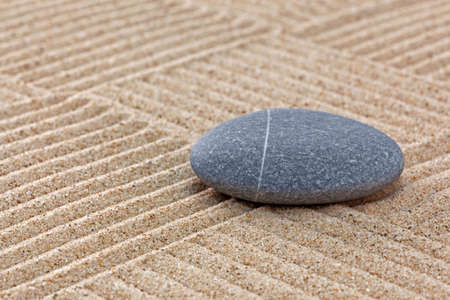 A pebble on a raked sand zen garden with patchwork patterns. Stock Photo - 18367364