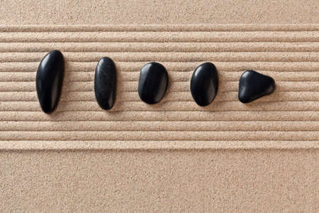 Five black pebbles on a raked sand zen garden. Stock Photo - 18367366