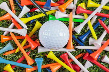 A golf ball amongst a collection of coloured wooden tees. Stock Photo - 18453496