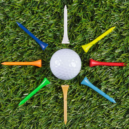 Golf ball with wooden tees arranged around it. Stock Photo - 18453497