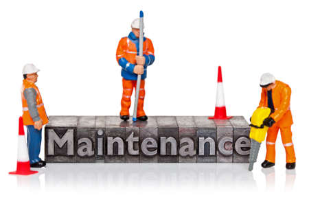 Hand painted miniature workmen figurines and the word Maintenance in old metal letterpress isolated on a white background.