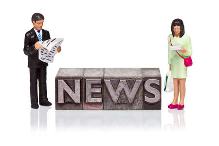 Hand painted business figurines and the word NEWS in old metal letterpress isolated on a white background. photo